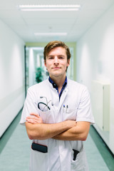 Friendly young doctor standing in the hall of a hospital with his arms crossed