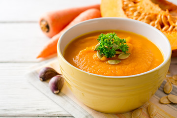 Pumpkin and carrot cream soup with pumpkin seeds and parsley in bowl on white wooden background.
