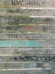 Graffiti markings on a wooden wall.