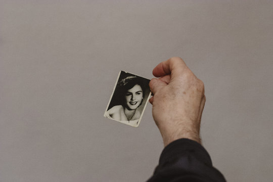 Senior Man Holding 50 Year Old Photo of His Wife