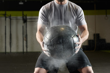 Fit man holding a weight ball in a  gym