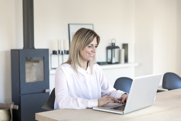 Businesswoman smiling whilst working on computer