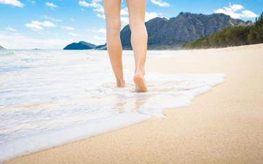 Woman walking on white sand beach. (Hawaii)