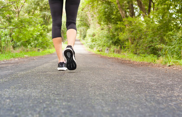 Closeup of woman's feet walking on country road.