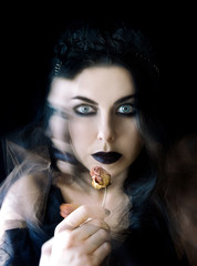darkhair gothic girl with black lips and dry rose in her hand