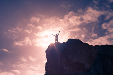 Man celebrating on top a mountain peak. Victory, challenge concept