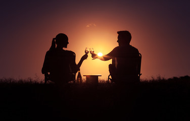 Romantic couple. Man woman relaxing outdoors, enjoying a glass of wine and beautiful sunset