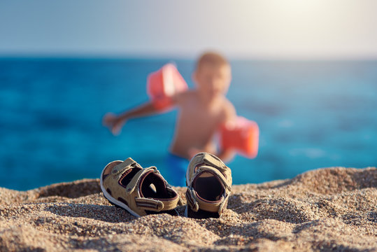 Children sandals on the beach sand against the sea with the unfocused boy on the background.