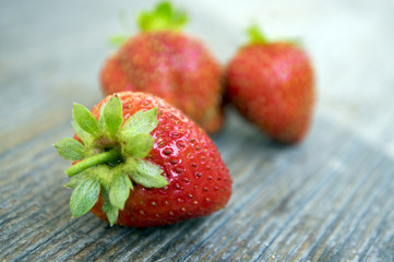 Ripe three red sweet strawberries on wooden table, isolated