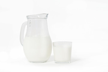 Jug and glass of milk on white background