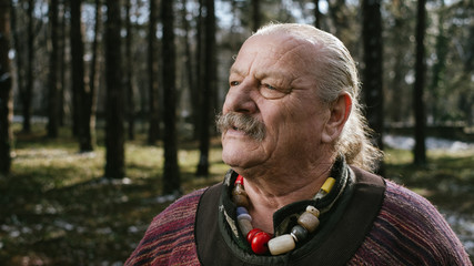 Portrait of eccentric old man in the forest