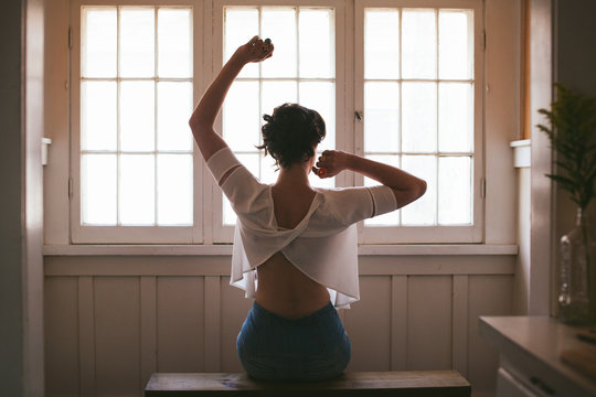 Girl in front of Window Stretching