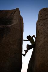 Woman silhouette climbing between two rock walls
