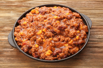 Chili con carne in frying pan on wooden background