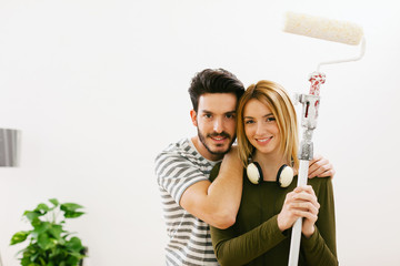 Portrait of young couple in love painting his new home.
