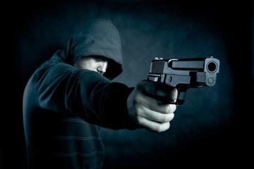 Hooded man with a gun in the dark  - fototapety na wymiar