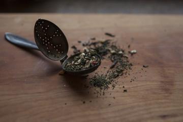 antique tea leaf spoon with loose tea leaves on wooden slat