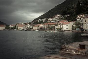 Promenade in old medieval port town Lapetane in rainy overcast day in Montenegro