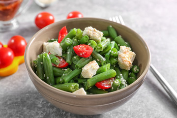 Bowl with delicious green beans salad on kitchen table