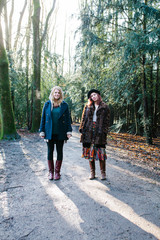 two young women standing on a path in the forest, looking at the camera