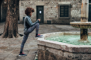 Young afro woman using phone while doing stretching exercises on the street.
