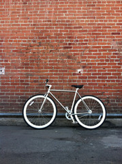 Fixed gear bicycle against red brick wall