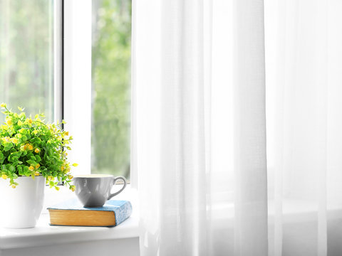 Green houseplant and book with cup of coffee on window sill in flat