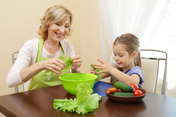 Cute little girl and her grandmother cooking on table