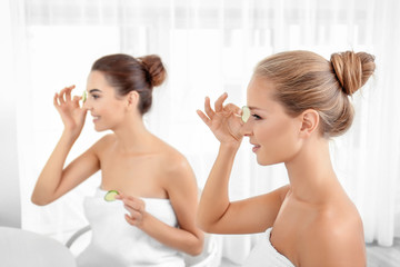 Young women with cucumber slices in bathroom