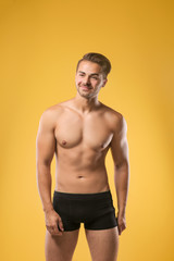 Sexy shirtless man in underwear on color background