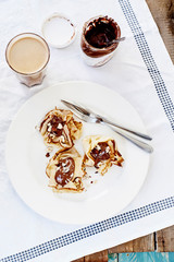 Pancakes with chocolate and coffee on white textile outdoor