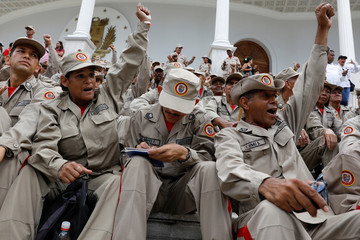 Militia members shout slogans at the courtyard on the grounds of the building housing the National Constituent Assembly before the swearing in ceremony for newly elected governors, in Caracas