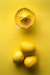 Lemons and juice extractor on yellow background