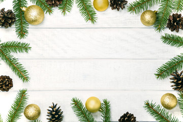 White wooden Christmas background. Border decorated fir branches and pin cones. Copy space for holiday greetings. lovely xmas festive card. Top view. Flat