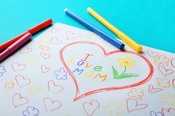 """Child's drawing with words """"I love mom"""" on color background, closeup"""