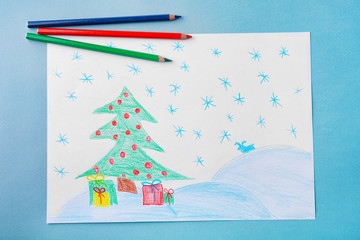 Child's drawing of Christmas tree with presents on grey background