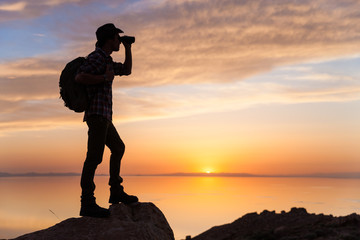 Sunset Silhouette of Backpacker Searching With Binoculars