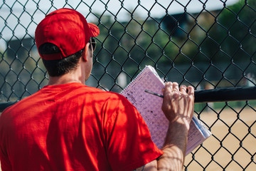 Baseball coach in red shirt and cap watching a game