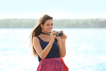 Beautiful young tourist with camera standing on river bank