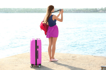 Beautiful young tourist with camera and suitcase standing on river bank
