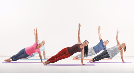 Group of mature people at yoga lesson indoors