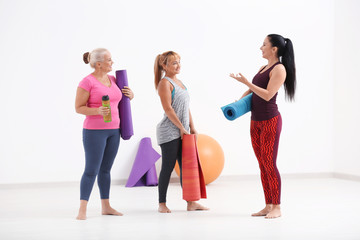 Women with yoga mats indoors