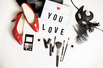 Top view to female accessories: red shoes with high heels, make up set, a mask, a note I love you