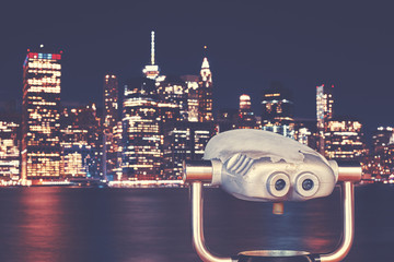 New York City skyline with binoculars at night, color toning applied, focus on foreground, USA.