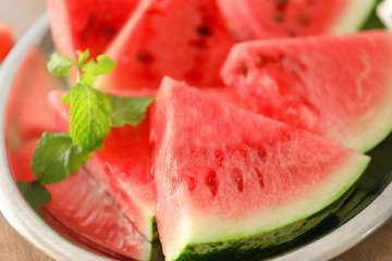 Plate with tasty sliced watermelon on table, closeup