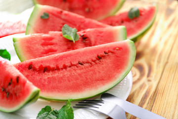 Plate with slices of tasty watermelon on table
