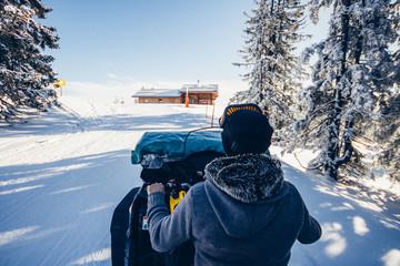 man driving snowmobile in snowcoverd austrian landscape