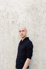 Portrait of Young Bald Caucasian Man Wearing Blue Sweater Standing in Front of White Wall