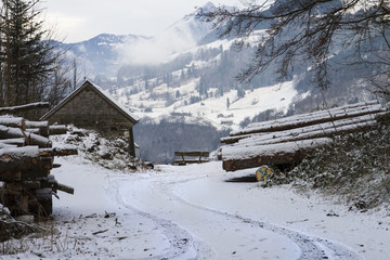 TIMBER FARMER BARN HOUSE IN WINTER MOUNTAIN SNOW COVERED LANDSCAPE IN OBERSEE, SWITZERLAND