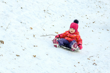 Little cute caucasian girl having fun sledding in a forest or city park on a brighht sunny day. Winter children activity concept